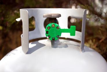 white propane tank with green nozzle