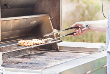 someone cooking chicken on a grill in the summertime