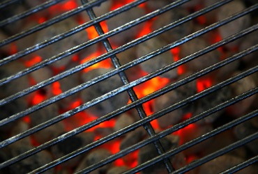 charcoal grill grates with embers lit underneath