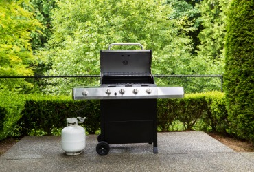 propane grill sitting on a backyard patio
