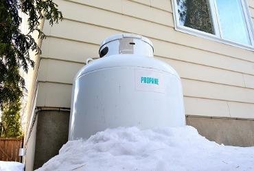 white propane tank sitting next to house in the snow