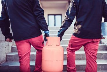 men in black jackets carrying an orange propane tank