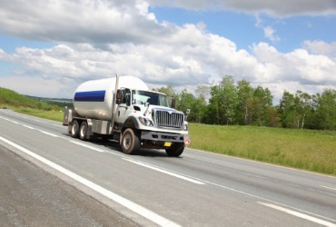 propane tanker truck driving down highway making a delivery