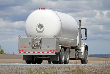 white propane truck driving down the road