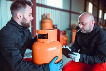 men in black jackets handing each other an orange propane tank in a warehouse